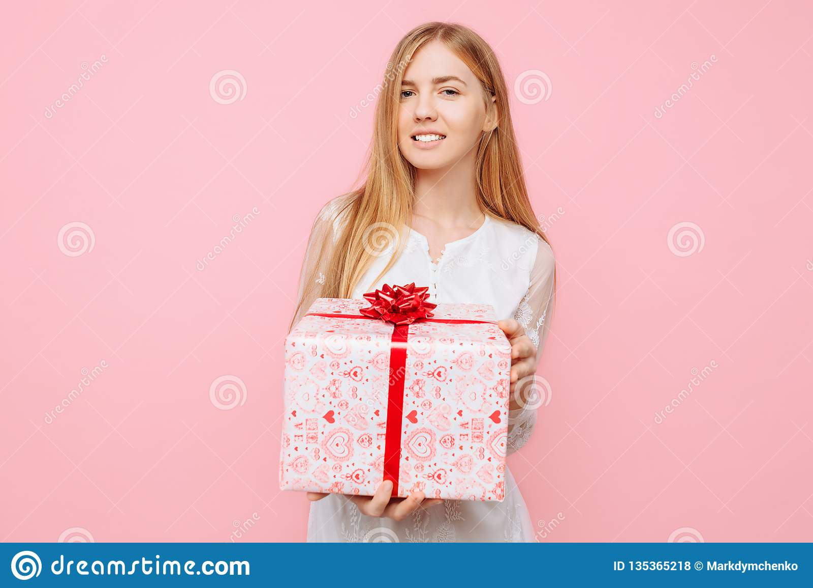 Ευτυχές νέο κορίτσι, σε ένα άσπρο φόρεμα, με ένα κιβώτιο δώρων υπό εξέταση, στο δέο του δώρου, σε ένα ρόδινο υπόβαθρο