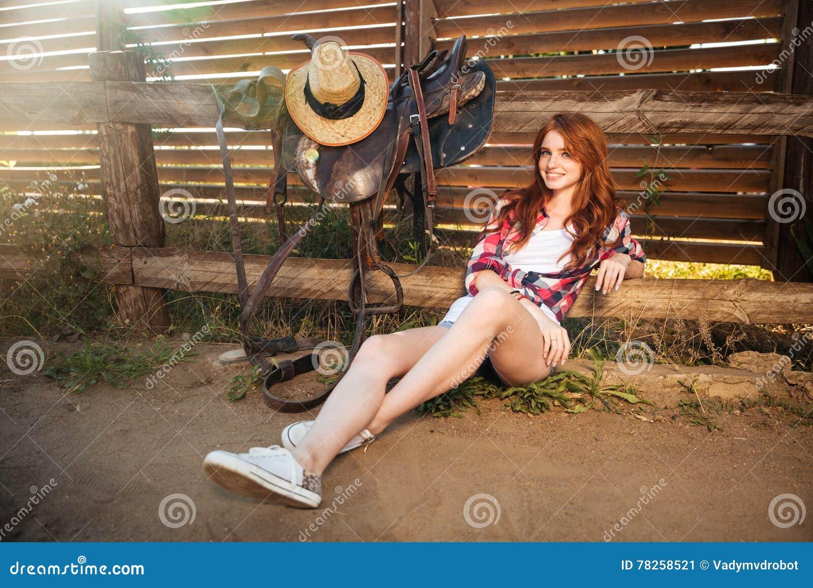 Ευτυχές νέο cowgirl χαμόγελου που στηρίζεται στο φράκτη αγροκτημάτων