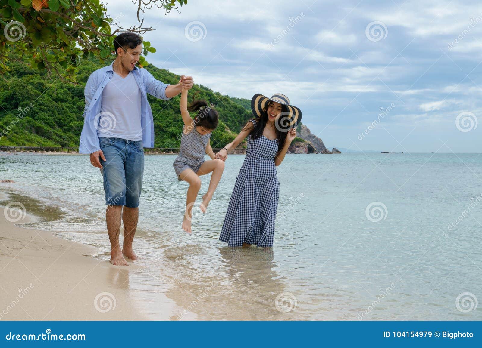 Ευτυχές οικογενειακό παιχνίδι στην παραλία στο χρόνο ημέρας