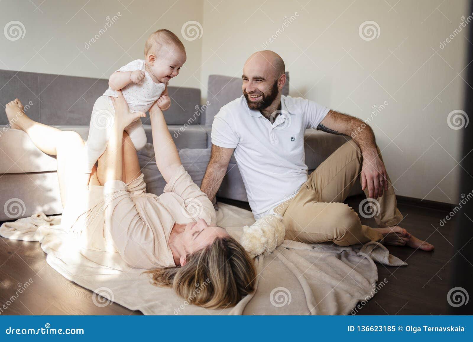 Ευτυχές παιχνίδι οικογενειών, μητέρων και πατέρων με μια μικρή κόρη στο σπίτι διάστημα αντιγράφων Γυναίκα που βρίσκεται στο πάτωμ