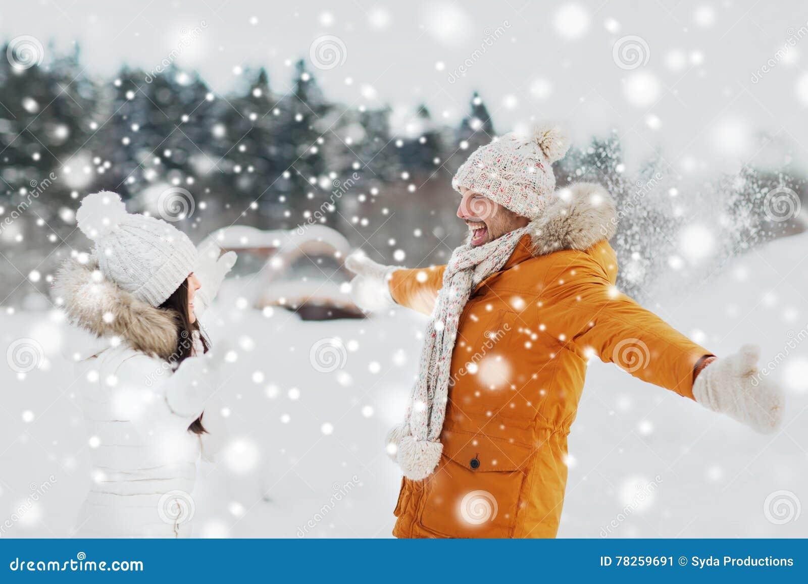 Ευτυχές παιχνίδι ζευγών με το χιόνι το χειμώνα