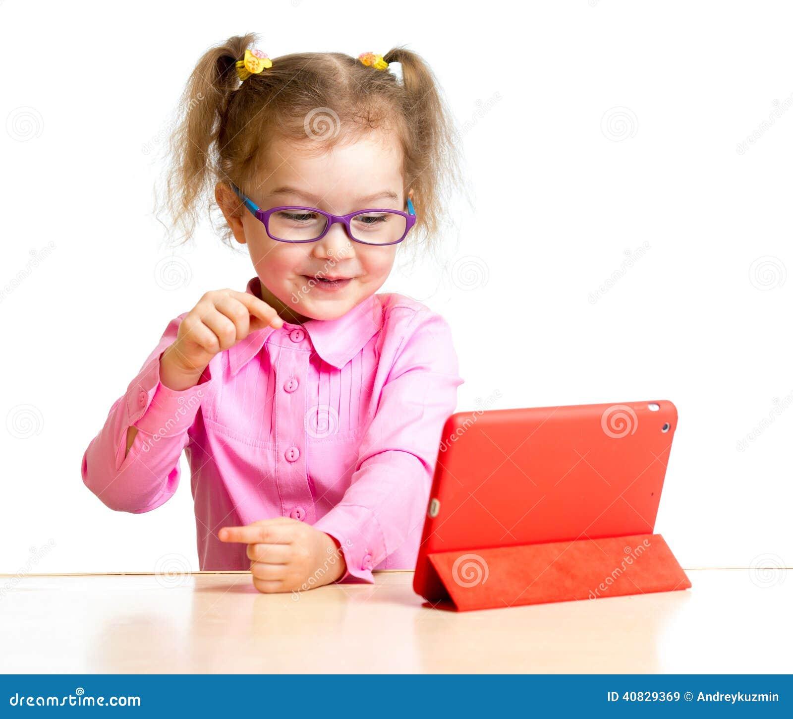 Ευτυχές παιδί στα γυαλιά που εξετάζει τη μίνι οθόνη PC ταμπλετών ipad