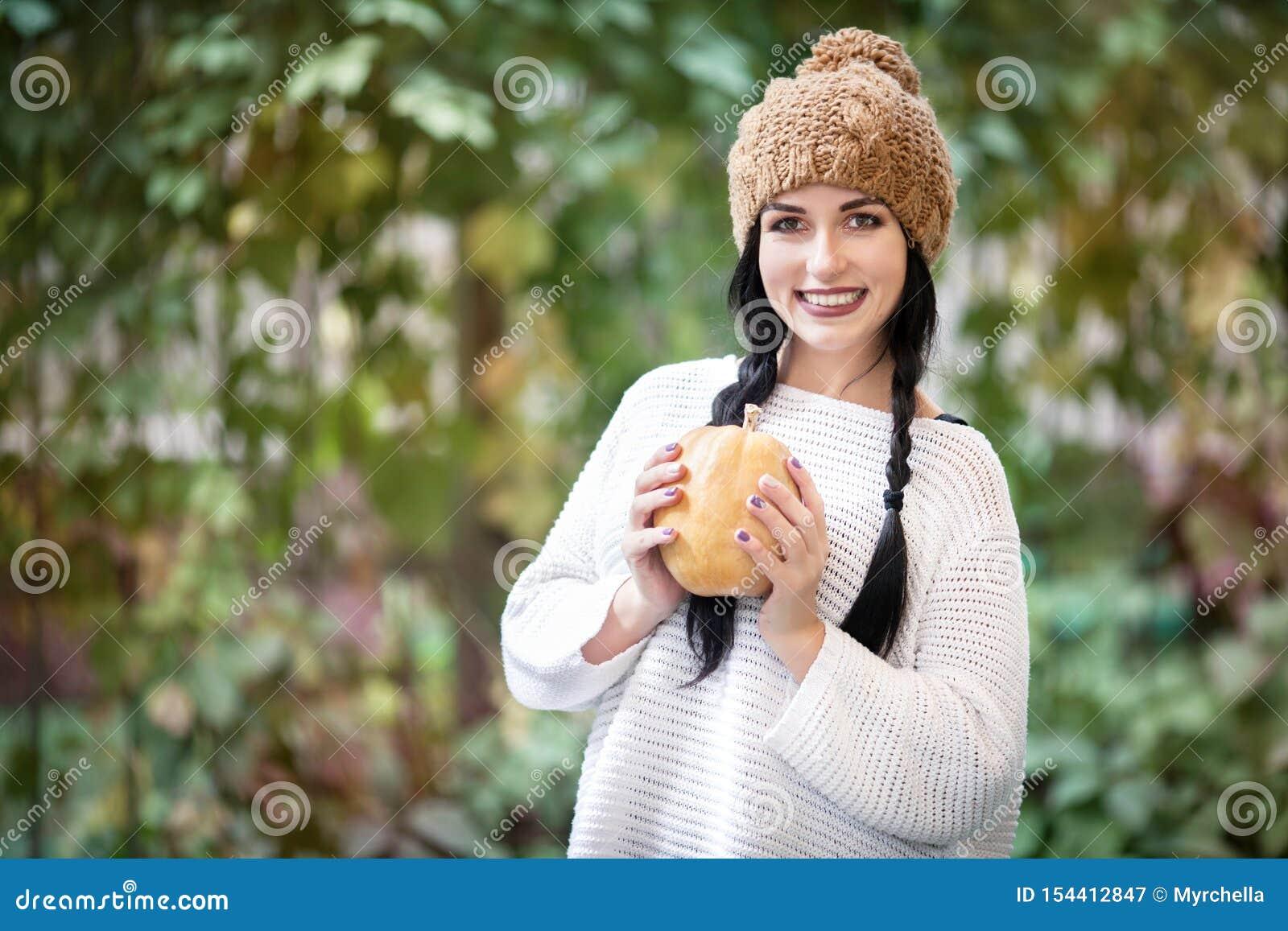 Ευτυχές πορτρέτο τρόπου ζωής μιας όμορφης νέας πρότυπης γυναίκας με μια κολοκύθα στα χέρια της