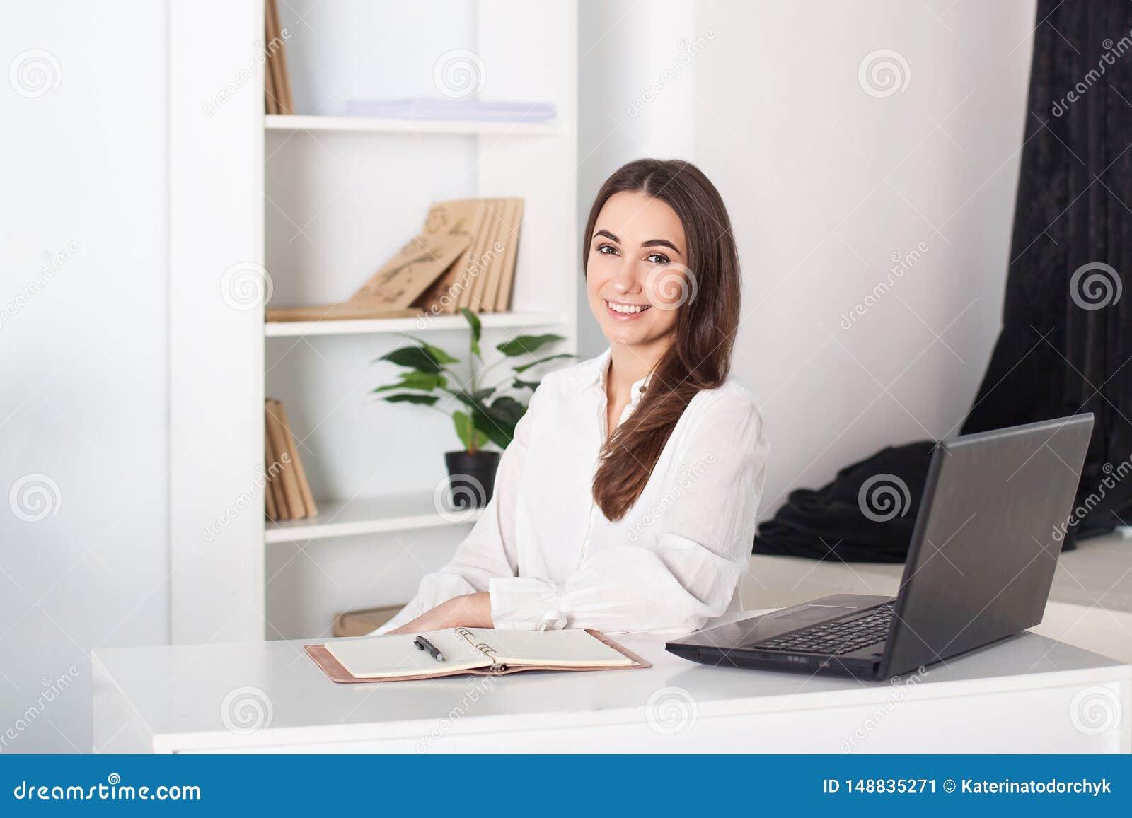 Ευτυχές χαμογελώντας νέο κορίτσι που εργάζεται στο γραφείο Πορτρέτο κινηματογραφήσεων σε πρώτο πλάνο ενός εργαζομένου γραφείων Θε