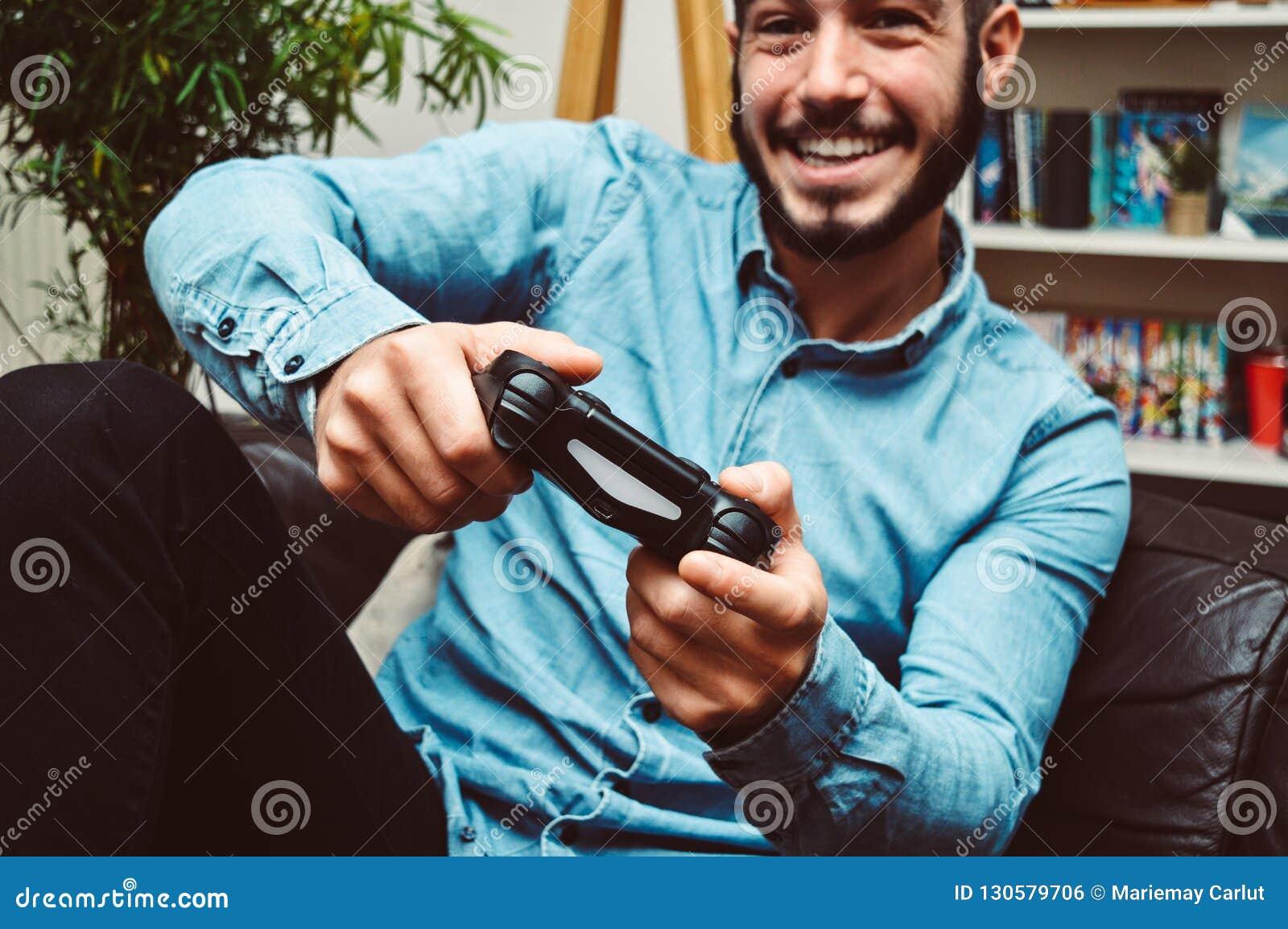 Ευτυχές χαμογελώντας νέο όμορφο άτομο που παίζει τα τηλεοπτικά παιχνίδια και που έχει τη διασκέδαση στο σπίτι