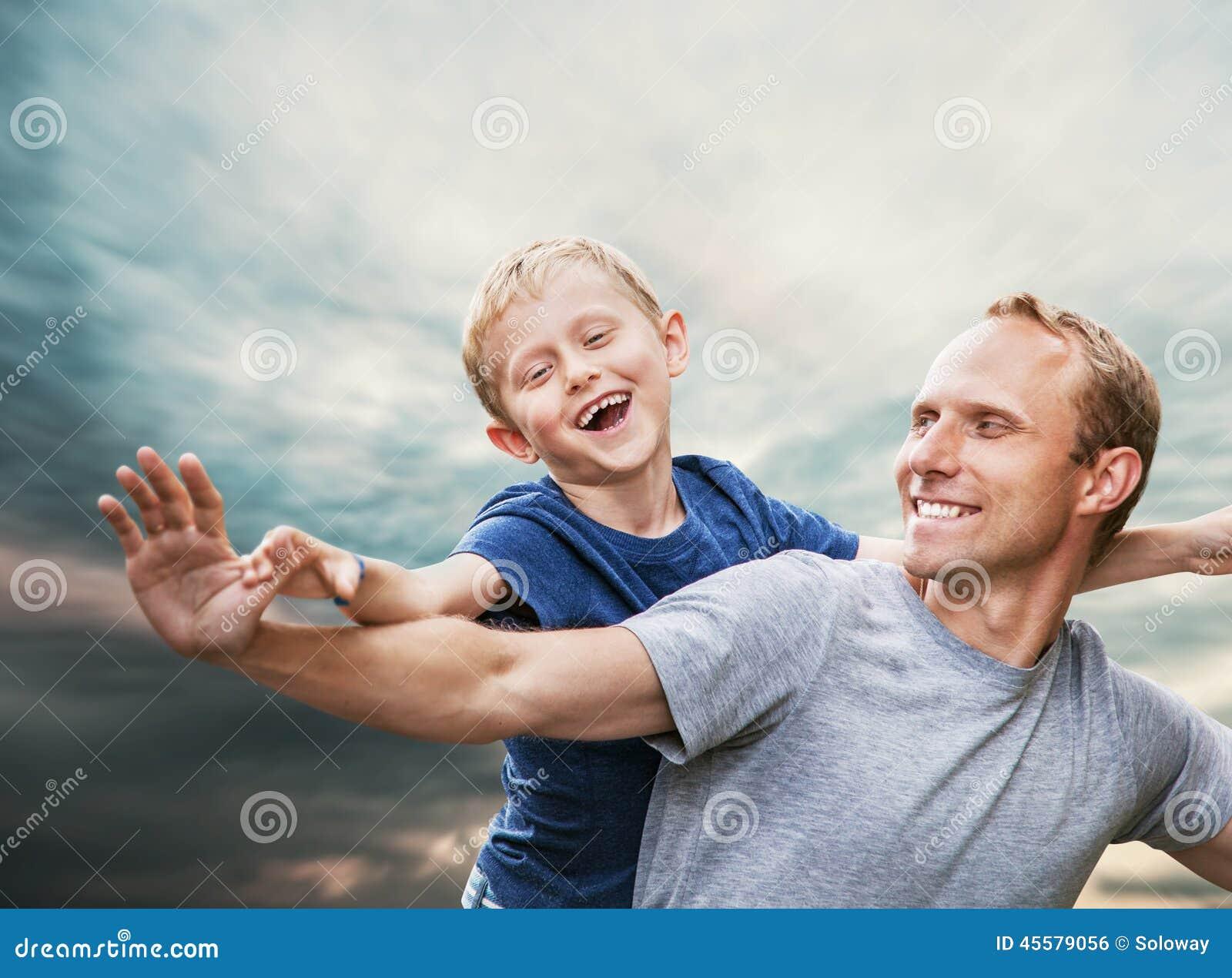 Ευτυχές χαμογελώντας πορτρέτο γιων και πατέρων πέρα από το μπλε ουρανό