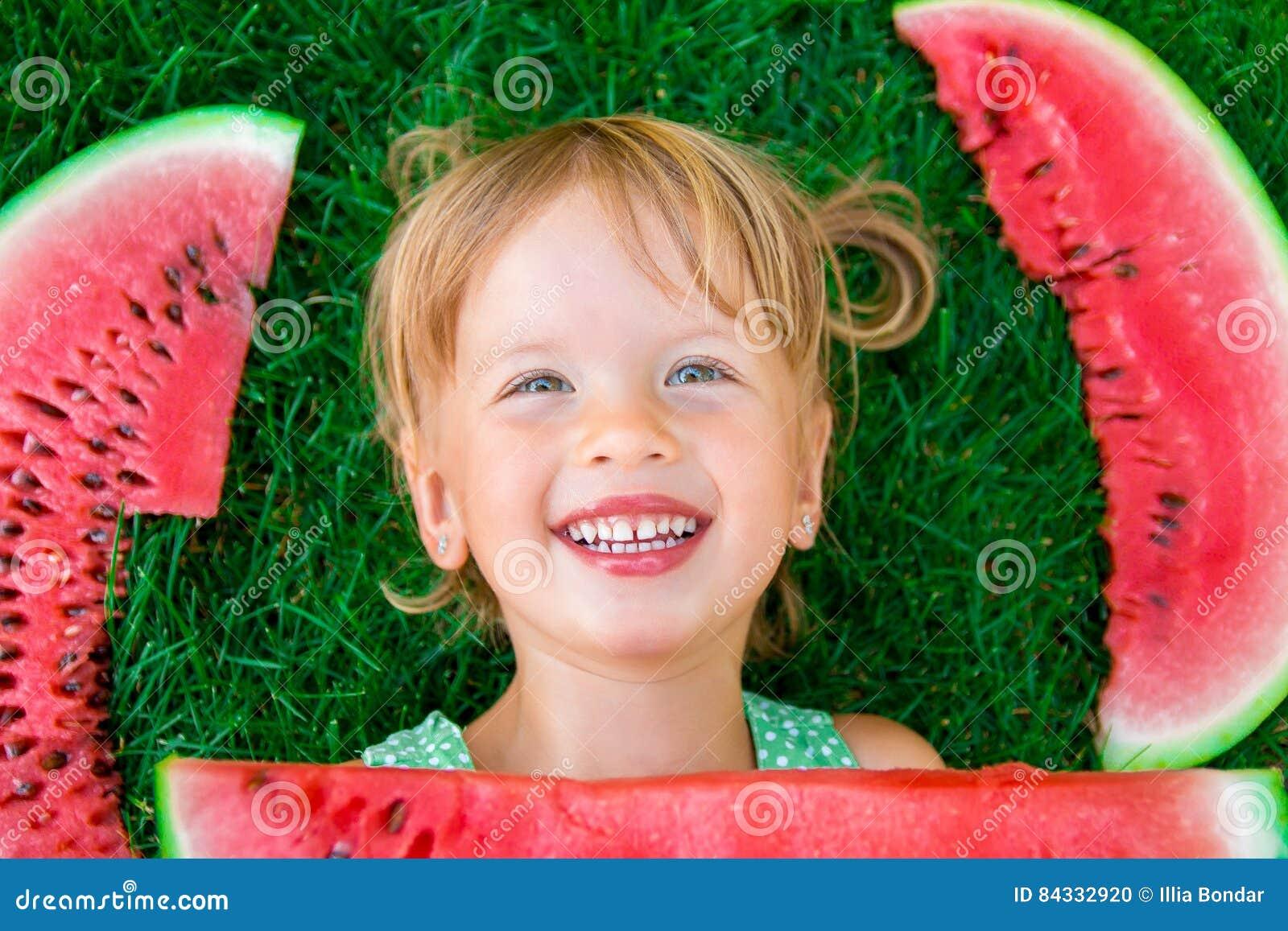 Ευτυχής λίγο ξανθό κορίτσι που βρίσκεται στη χλόη με το μεγάλο καρπούζι φετών στο θερινό χρόνο Χαμόγελο Τοπ όψη