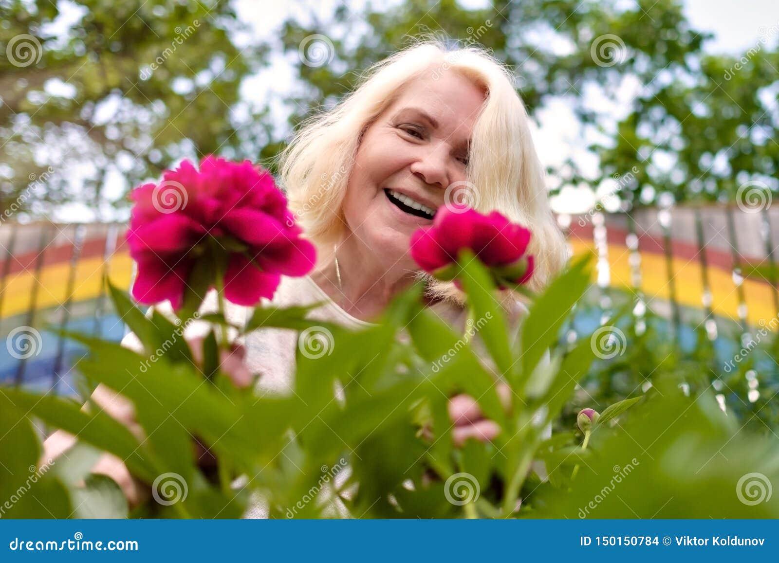Ευτυχής ανώτερη γυναίκα με τα λουλούδια που ανθίζουν στο θερινό κήπο