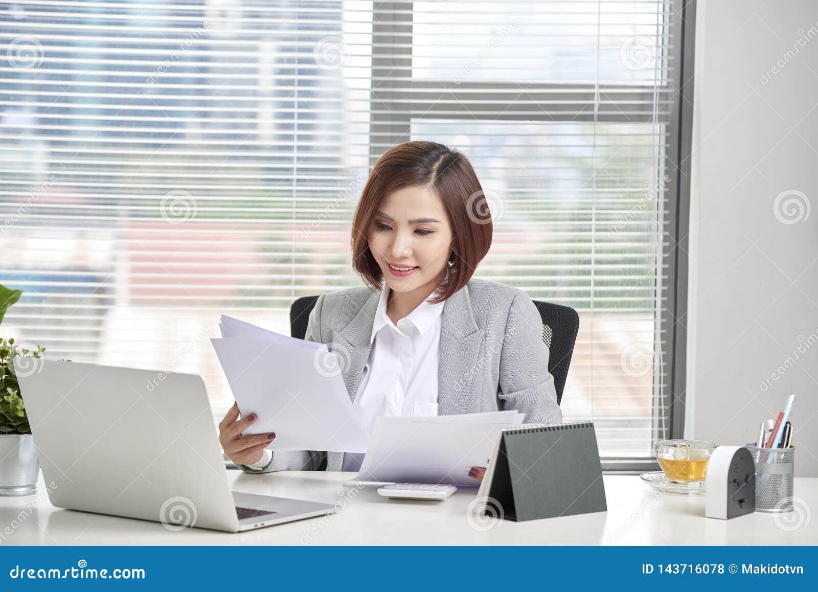 Ευτυχής ασιατική εργασία γυναικών στην αρχή Θηλυκό που περνά από κάποια γραφική εργασία στο χώρο εργασίας