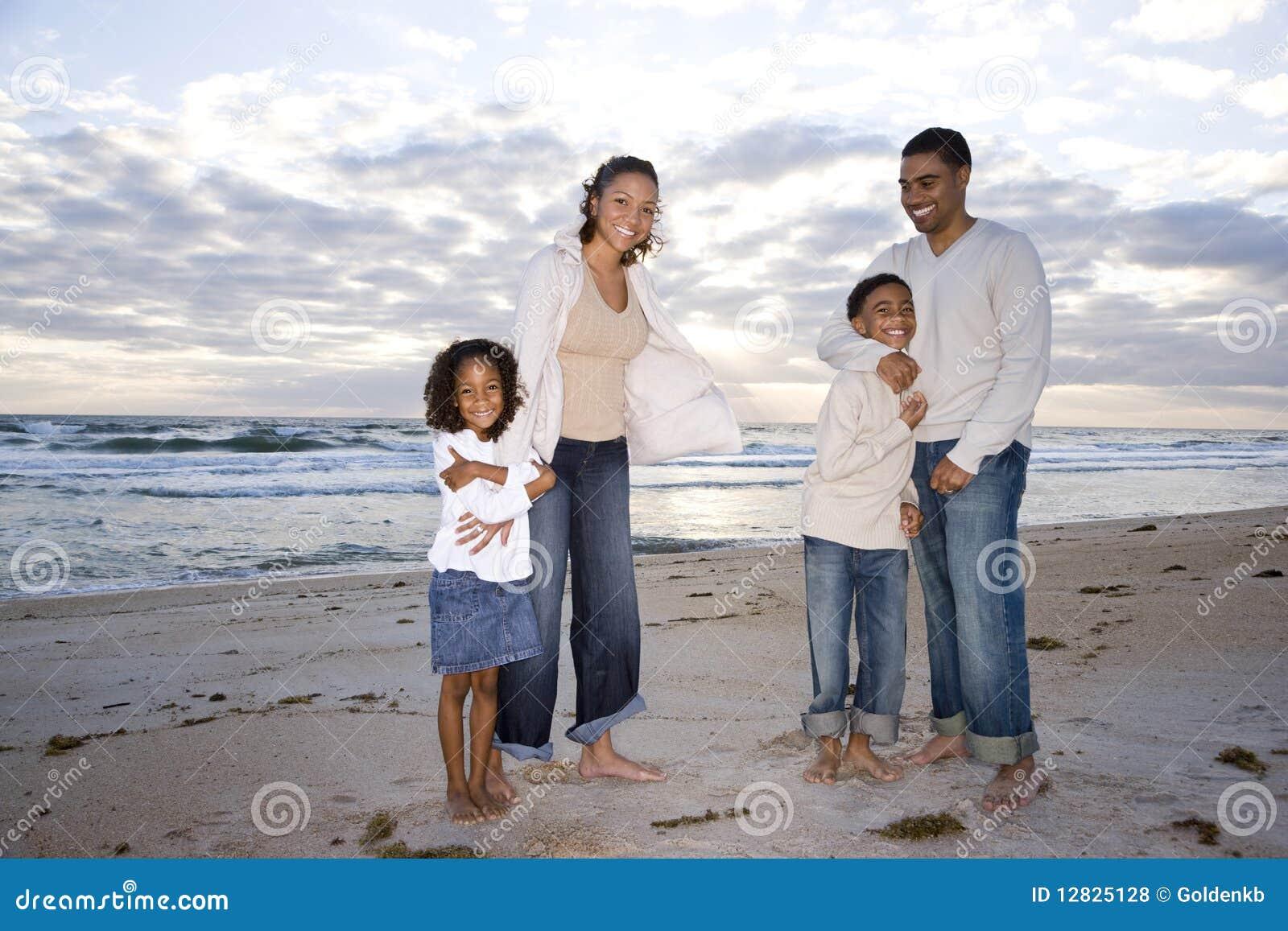 Ευτυχής αφρικανικός-αμερικανική τετραμελής οικογένεια στην παραλία