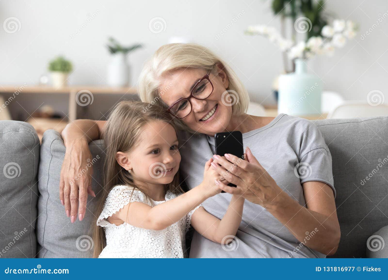 Ευτυχής γιαγιά και χαριτωμένη εγγονή που χρησιμοποιούν την κατασκευή κινητών τηλεφώνων