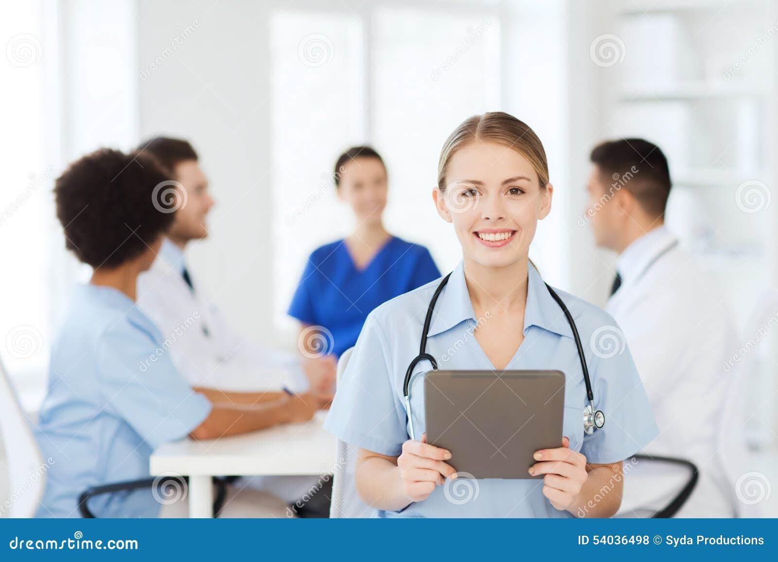 Ευτυχής γιατρός με το PC ταμπλετών πέρα από την ομάδα στην κλινική