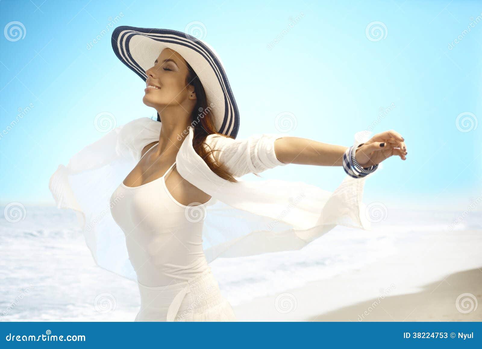Ευτυχής γυναίκα που απολαμβάνει το θερινό ήλιο στην παραλία