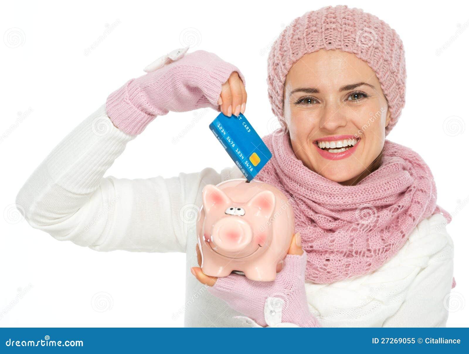 Ευτυχής γυναίκα που βάζει την πιστωτική κάρτα στη piggy τράπεζα