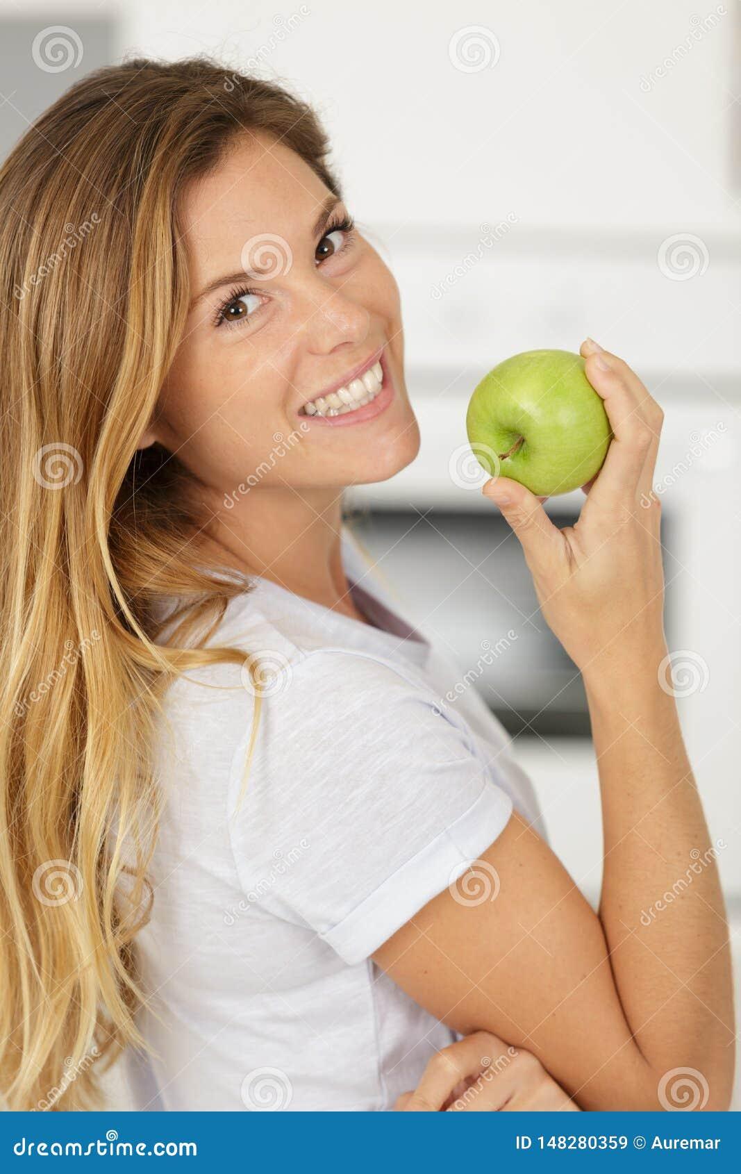Ευτυχής γυναίκα που δαγκώνει το πράσινο μήλο