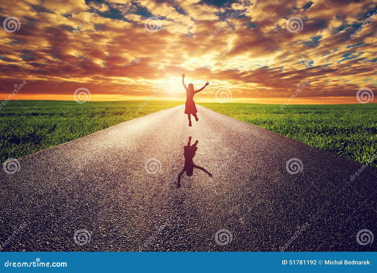 Ευτυχής γυναίκα που πηδά στο μακρύ ευθύ δρόμο, τρόπος προς τον ήλιο ηλιοβασιλέματος