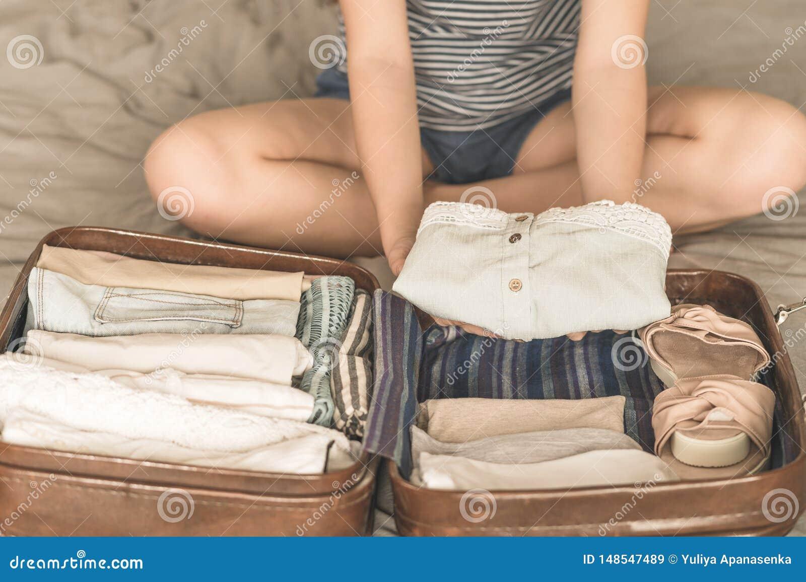 Ευτυχής γυναίκα που προγραμματίζει ένα ταξίδι που προετοιμάζει μια βαλίτσα
