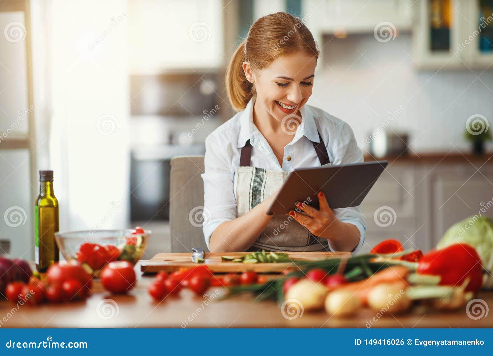 Ευτυχής γυναίκα που προετοιμάζει τα λαχανικά στην κουζίνα στη συνταγή με την ταμπλέτα