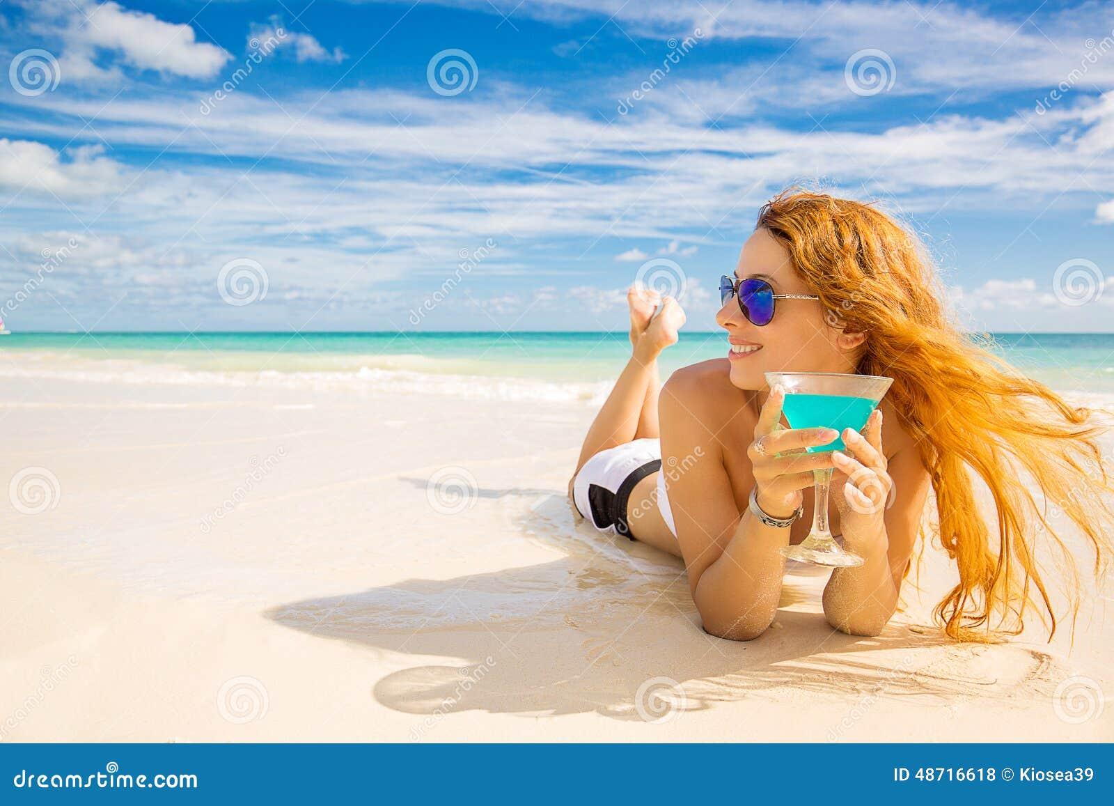 Ευτυχής γυναίκα στην παραλία που απολαμβάνει τον ηλιόλουστο καιρό