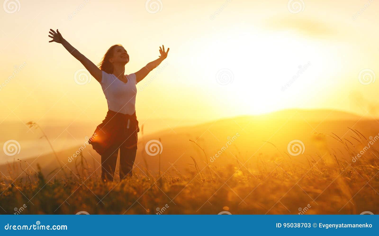 Ευτυχής γυναίκα στο ηλιοβασίλεμα στα ανοικτά χέρια φύσης iwith