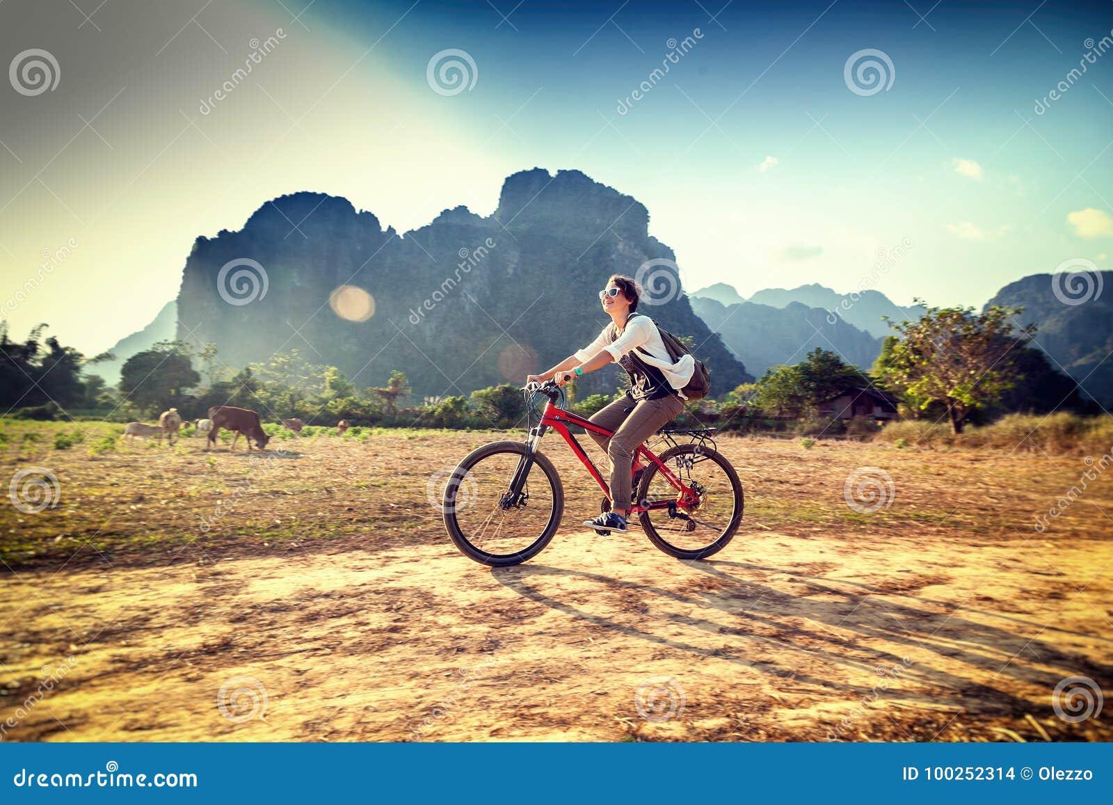 Ευτυχής γυναίκα τουριστών που οδηγά ένα ποδήλατο στην περιοχή βουνών στο Λάος Τ