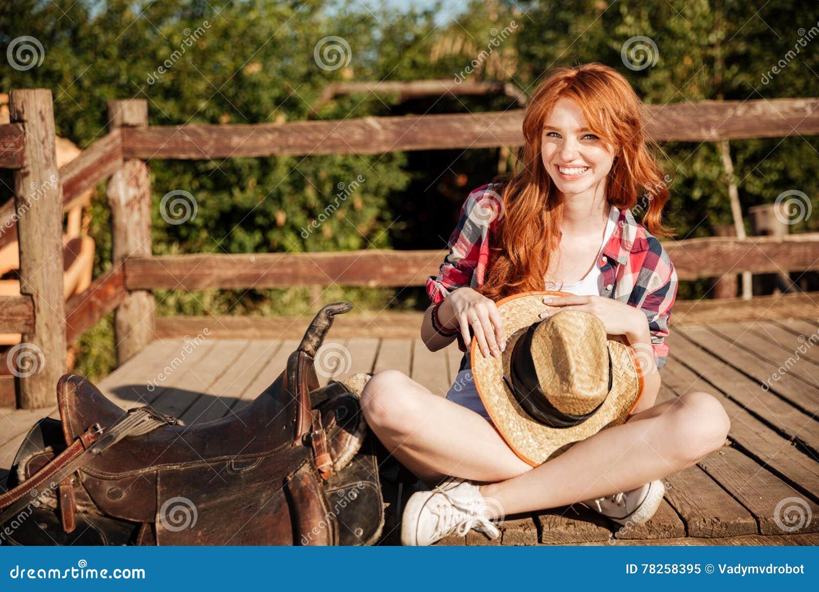 Ευτυχής γυναίκα cowgirl με τη συνεδρίαση καπέλων στο αγρόκτημα