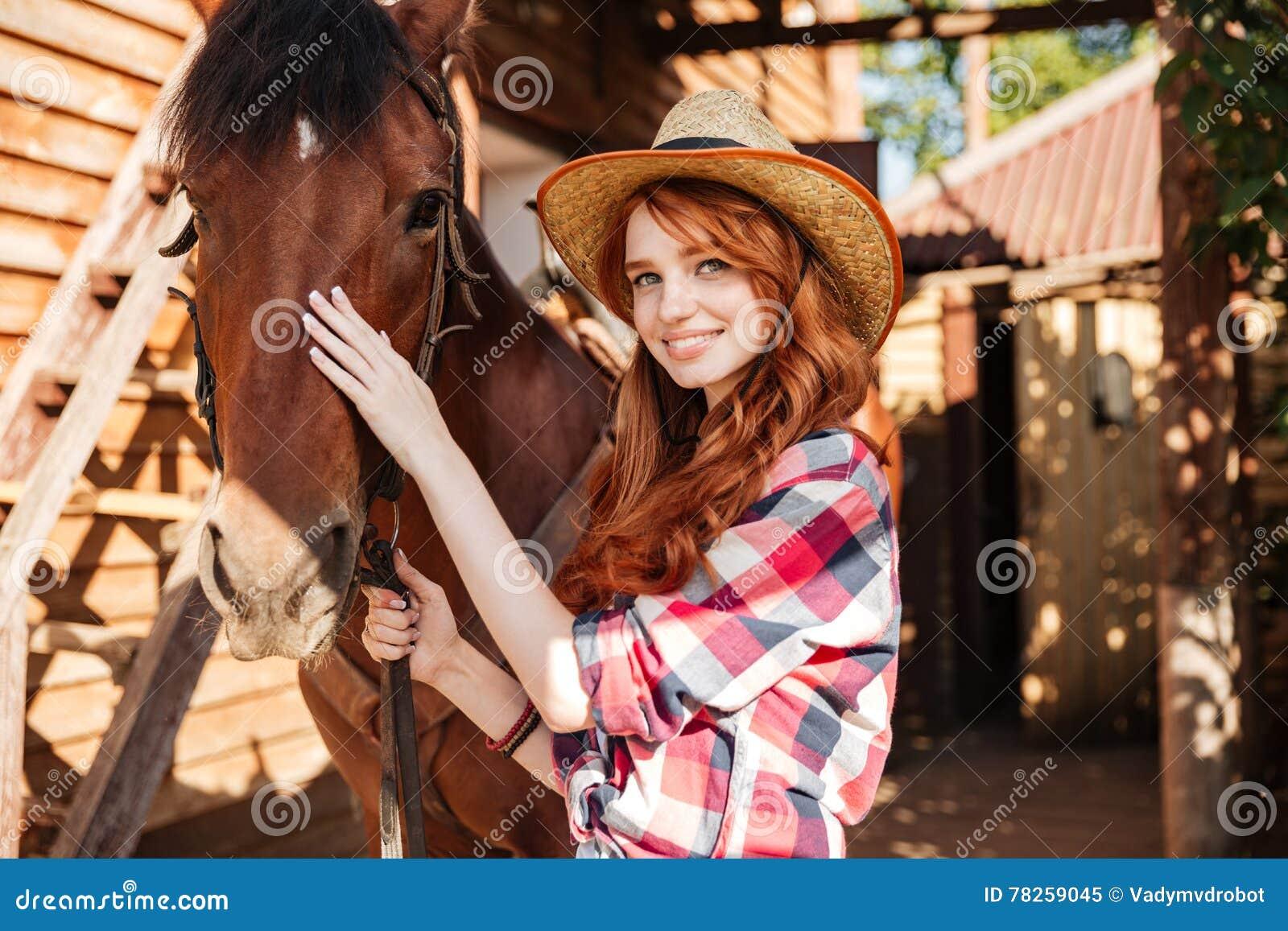 Ευτυχής γυναίκα cowgirl με το άλογό της στο χωριό