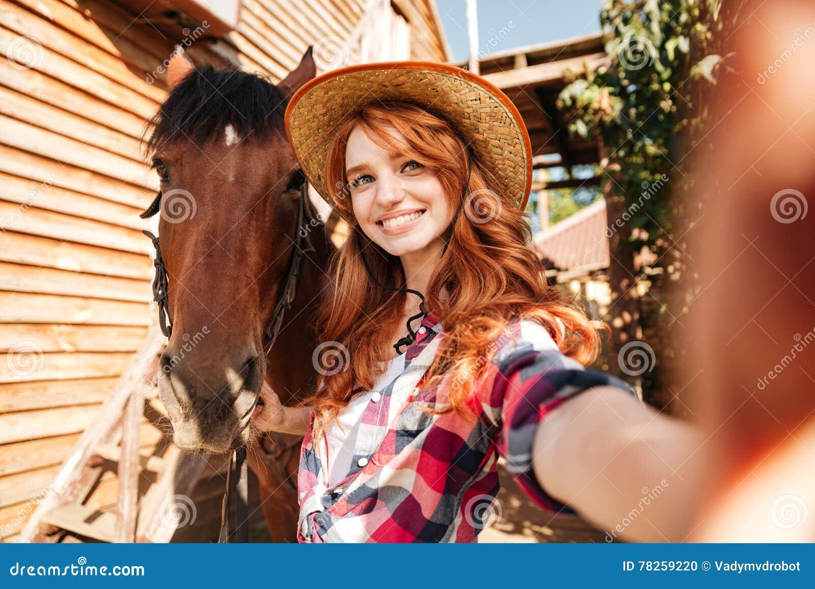 Ευτυχής γυναίκα cowgirl που παίρνει selfie με το άλογό της στο αγρόκτημα