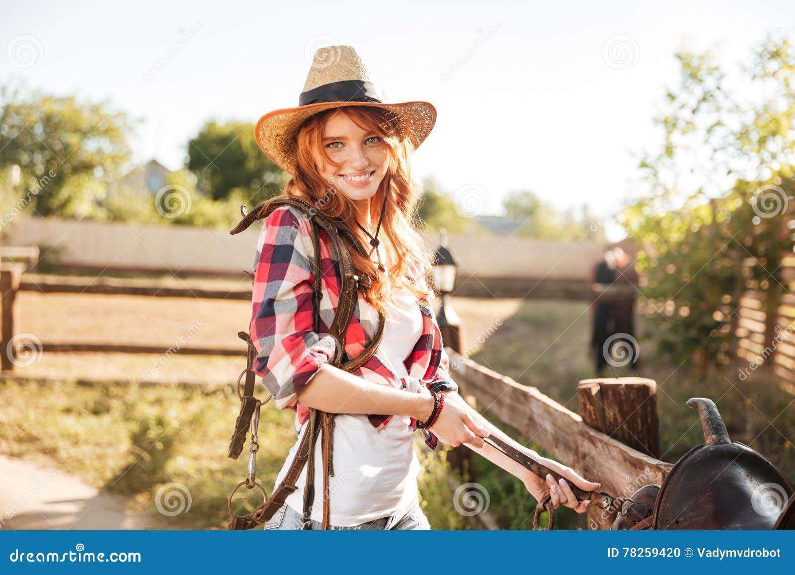 Ευτυχής γυναίκα cowgirl που προετοιμάζει τη σέλα για την οδήγηση του αλόγου