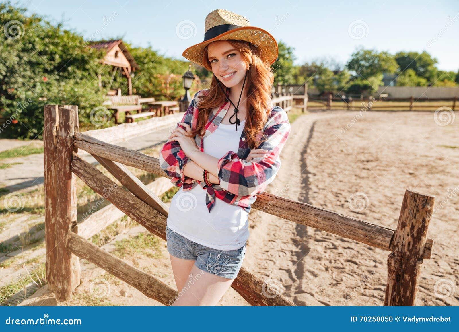 Ευτυχής γυναίκα cowgirl που στέκεται με τα χέρια που διπλώνονται