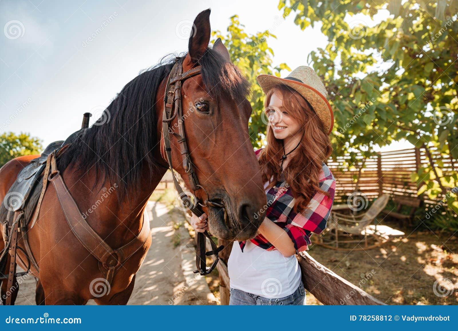 Ευτυχής γυναίκα cowgirl που φροντίζει το άλογό της στο αγρόκτημα
