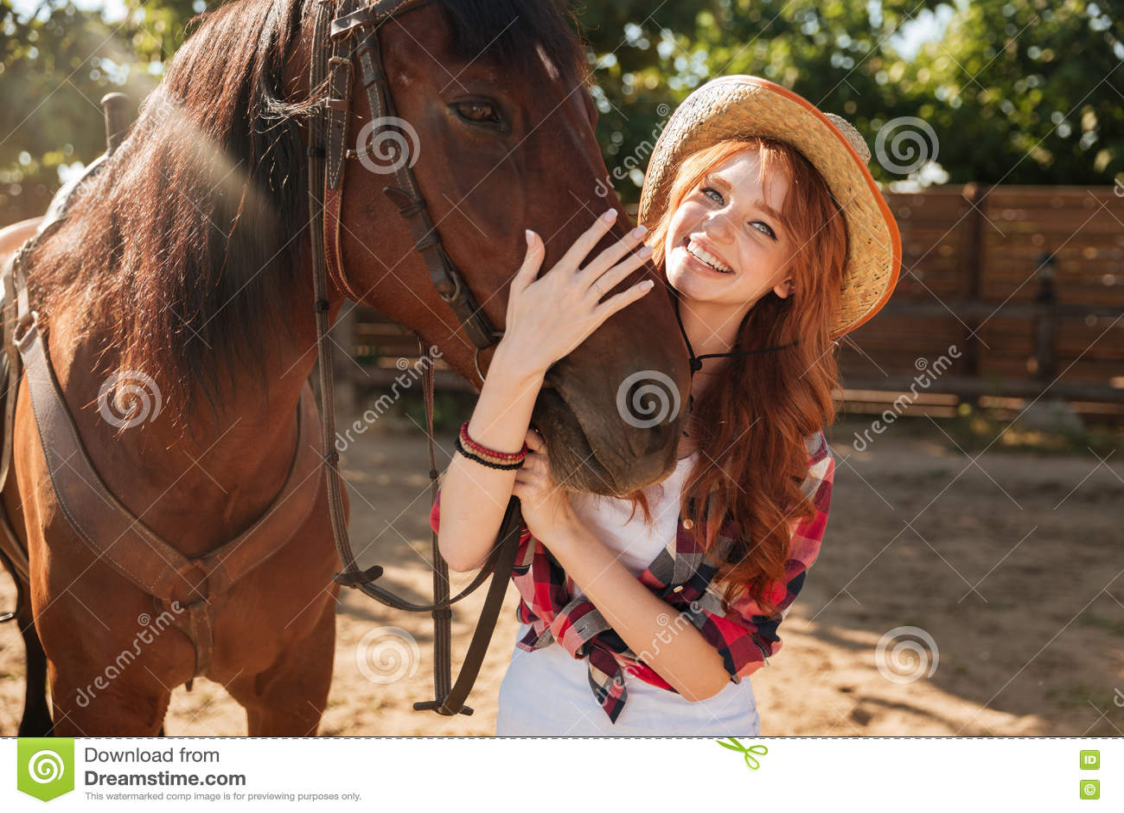 Ευτυχής γυναίκα cowgirl στο καπέλο που στέκεται και που αγκαλιάζει το άλογό της