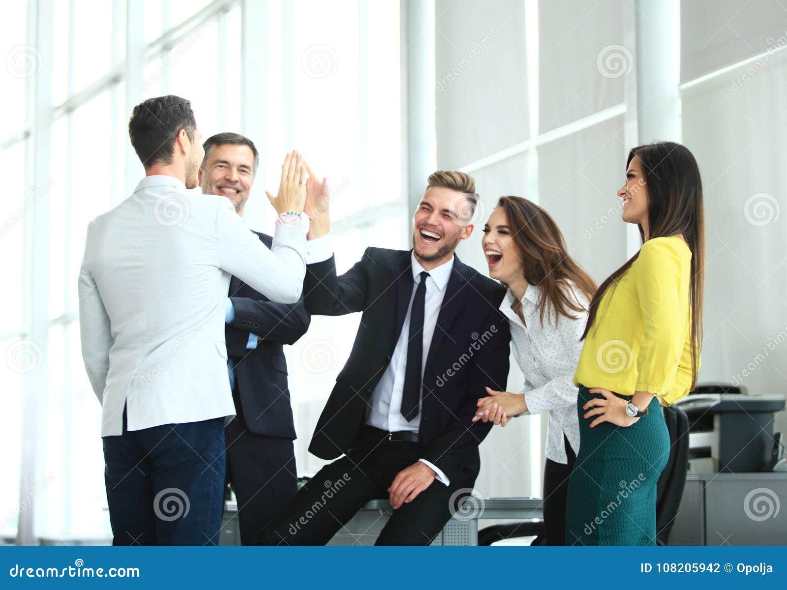 Ευτυχής επιτυχής πολυφυλετική επιχειρησιακή ομάδα που δίνει μια υψηλή χειρονομία fives καθώς γελούν και ευθυμία η επιτυχία τους