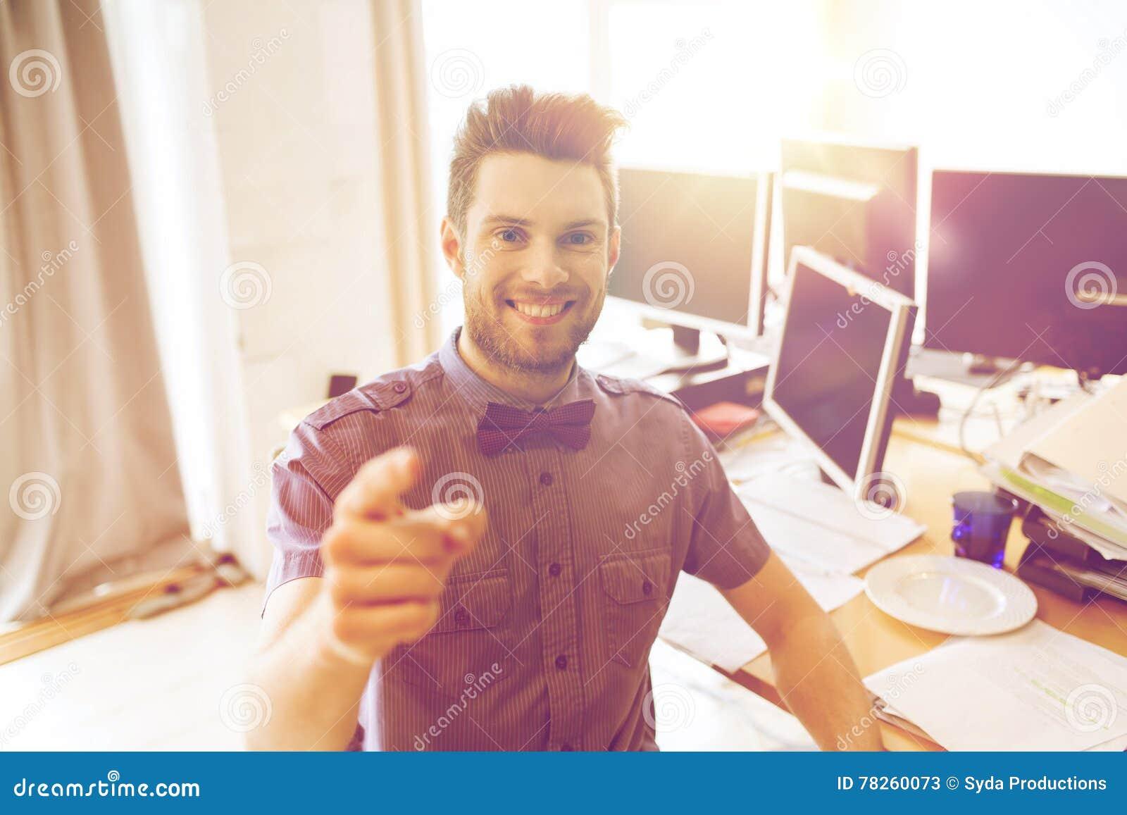 Ευτυχής εργαζόμενος γραφείων αρσενικών που δείχνει το δάχτυλο σε σας