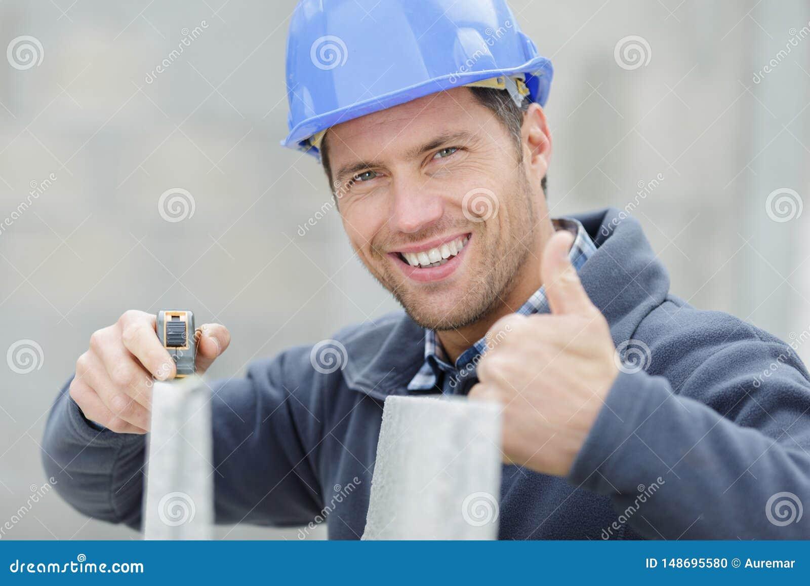 Ευτυχής εργαζόμενος πλινθοκτιστών κατασκευής υπαίθρια