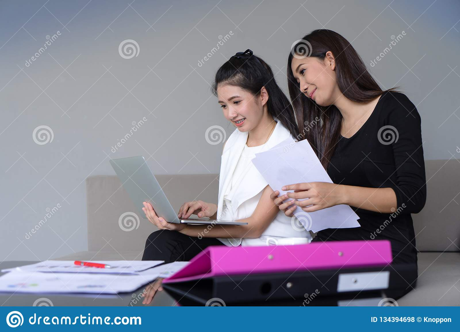 Ευτυχής εργασία δύο νέα επιχειρησιακών γυναικών μαζί με το lap-top στην αρχή
