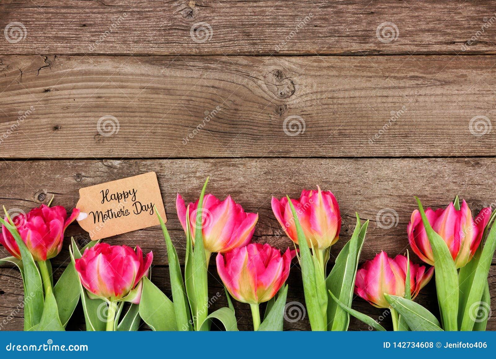 Ευτυχής ετικέττα ημέρας μητέρων με τα κατώτατα σύνορα των ρόδινων λουλουδιών σε ένα αγροτικό ξύλινο κλίμα