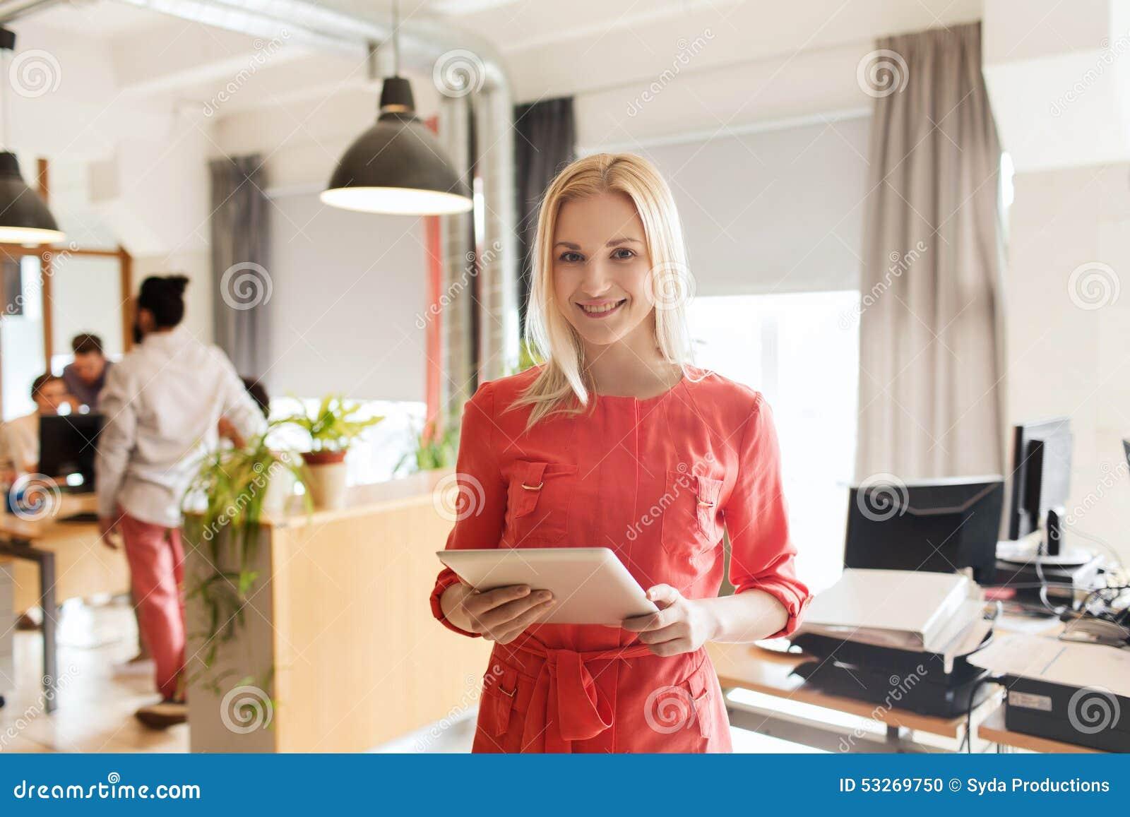 Ευτυχής δημιουργικός εργαζόμενος γραφείων θηλυκών με το PC ταμπλετών