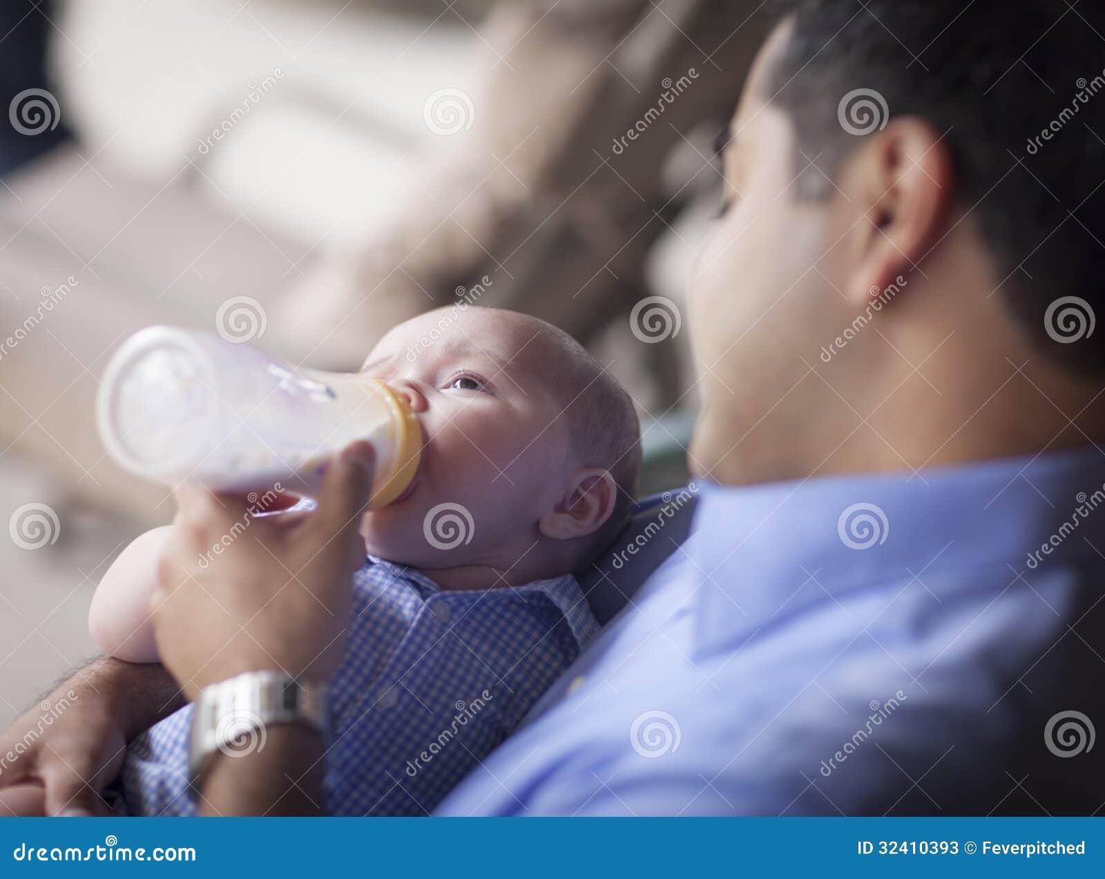 Ευτυχής ισπανικός πατέρας που ταΐζει με μπιμπερό το μικτό γιο φυλών του