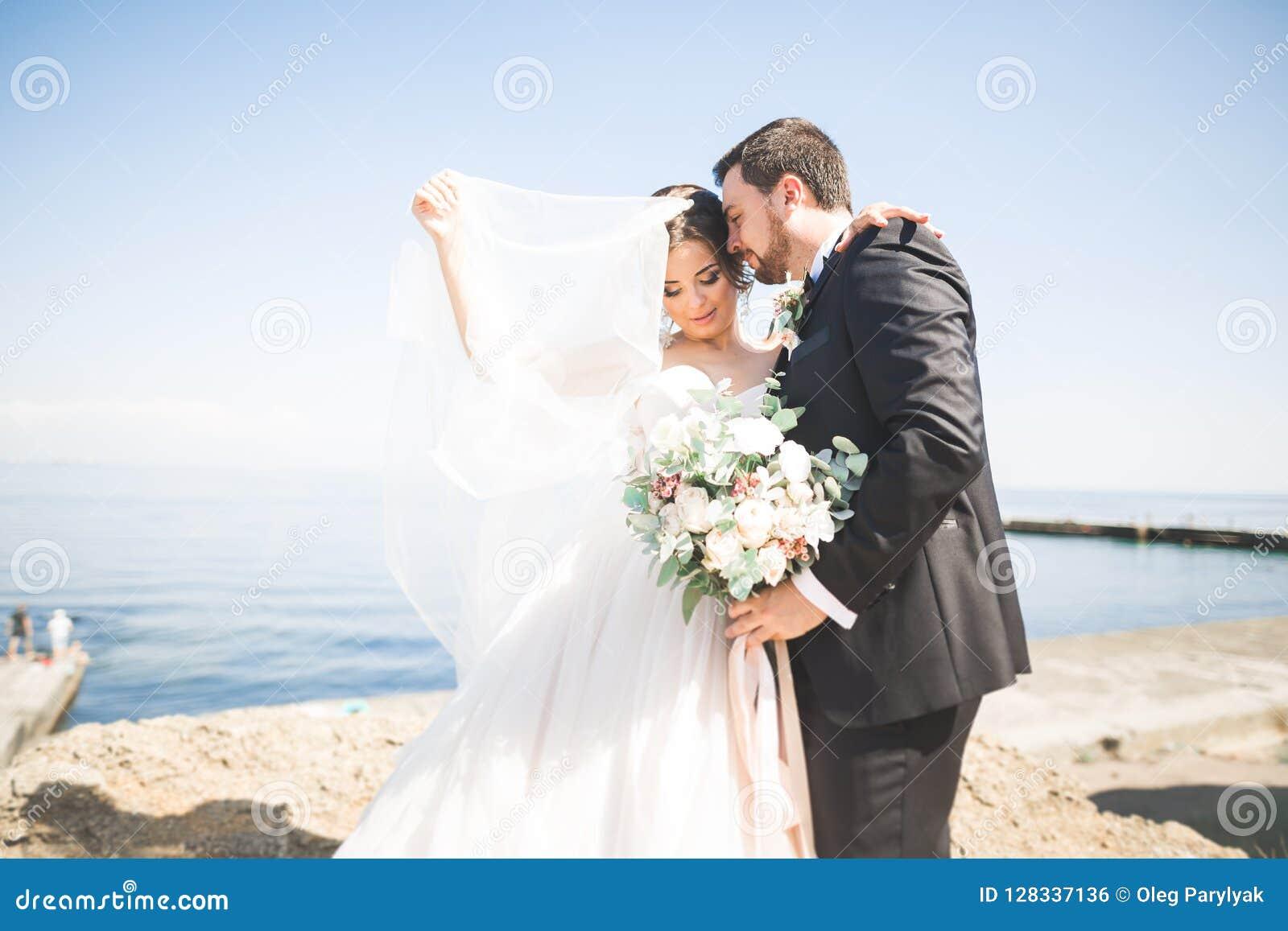 Ευτυχής και ρομαντική σκηνή ακριβώς της παντρεμένης νέας τοποθέτησης γαμήλιων ζευγών στην όμορφη παραλία