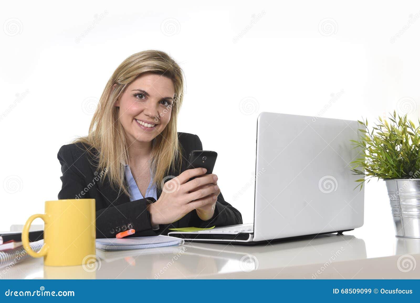 Ευτυχής καυκάσια ξανθή επιχειρησιακή γυναίκα που εργάζεται χρησιμοποιώντας το κινητό τηλέφωνο στο γραφείο υπολογιστών γραφείων