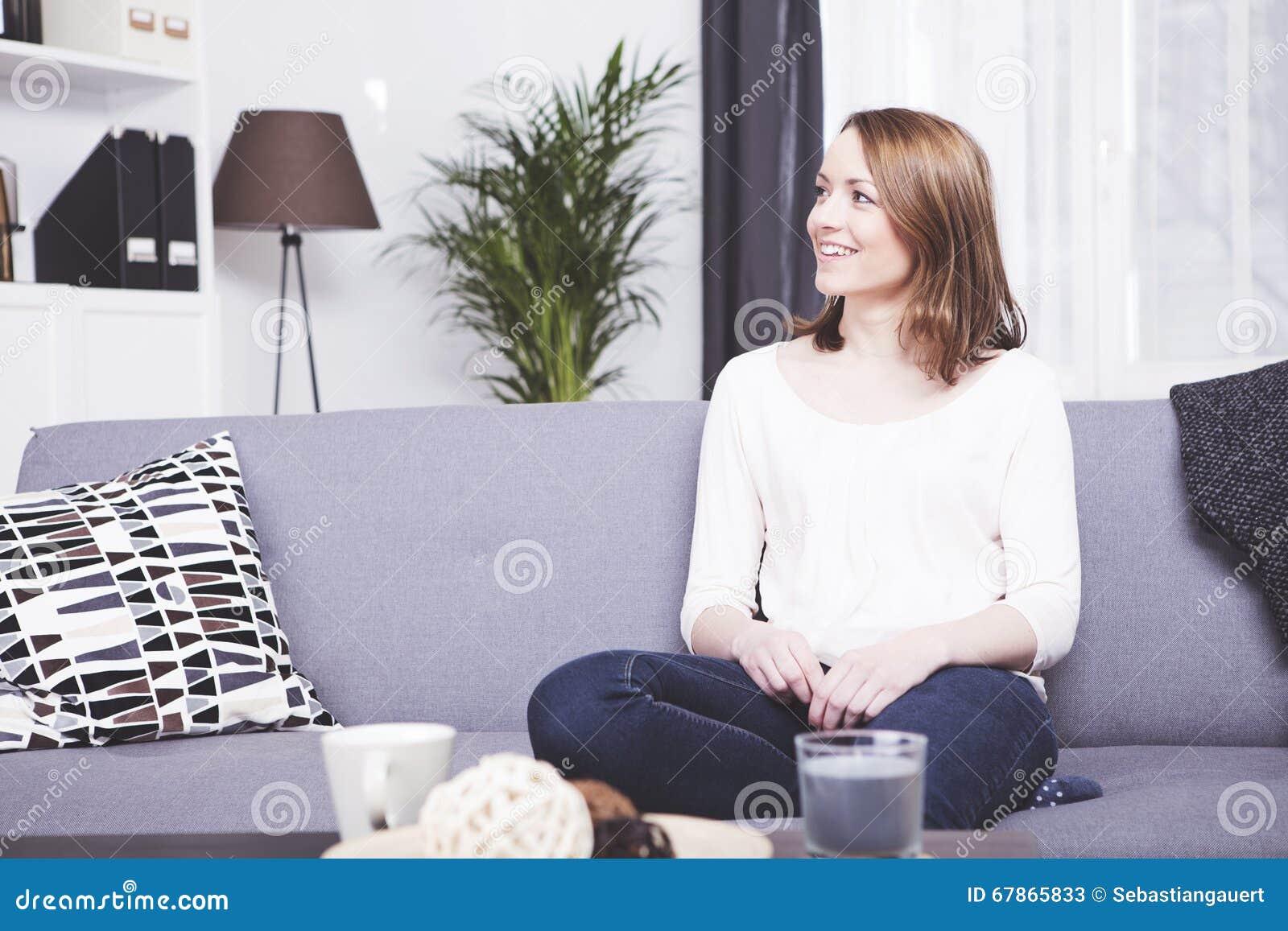Ευτυχής καφετιά μαλλιαρή συνεδρίαση κοριτσιών που χαμογελά σε έναν καναπέ