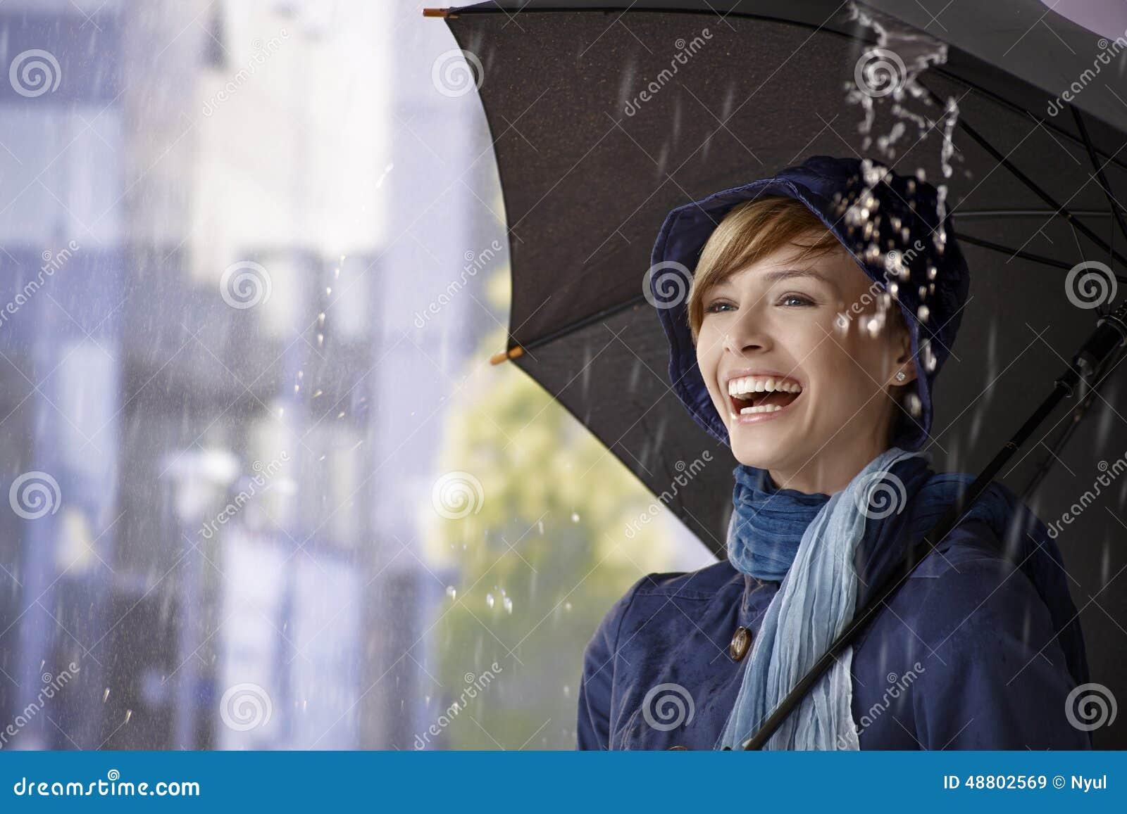 Ευτυχής νέα γυναίκα κάτω από την ομπρέλα στη βροχή