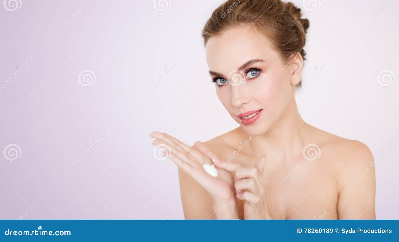 Ευτυχής νέα γυναίκα με την ενυδατική κρέμα σε διαθεσιμότητα