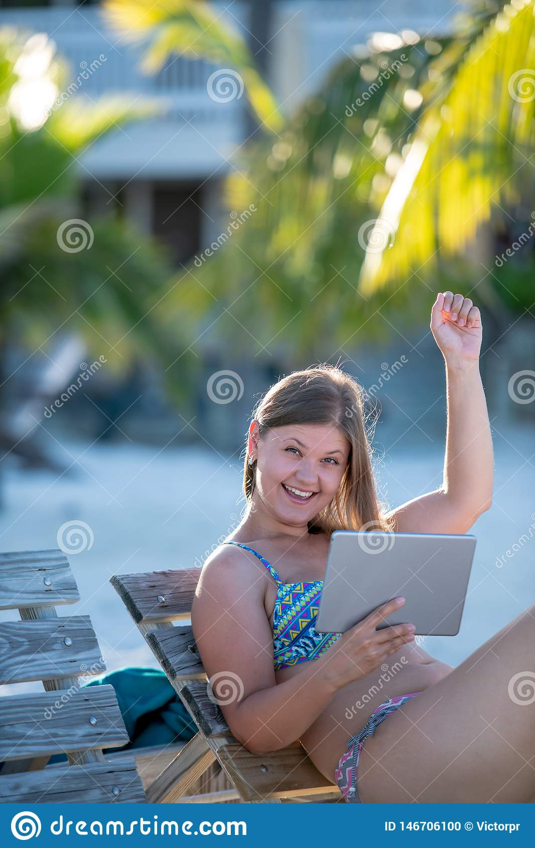 Ευτυχής νέα γυναίκα με την ταμπλέτα στην παραλία