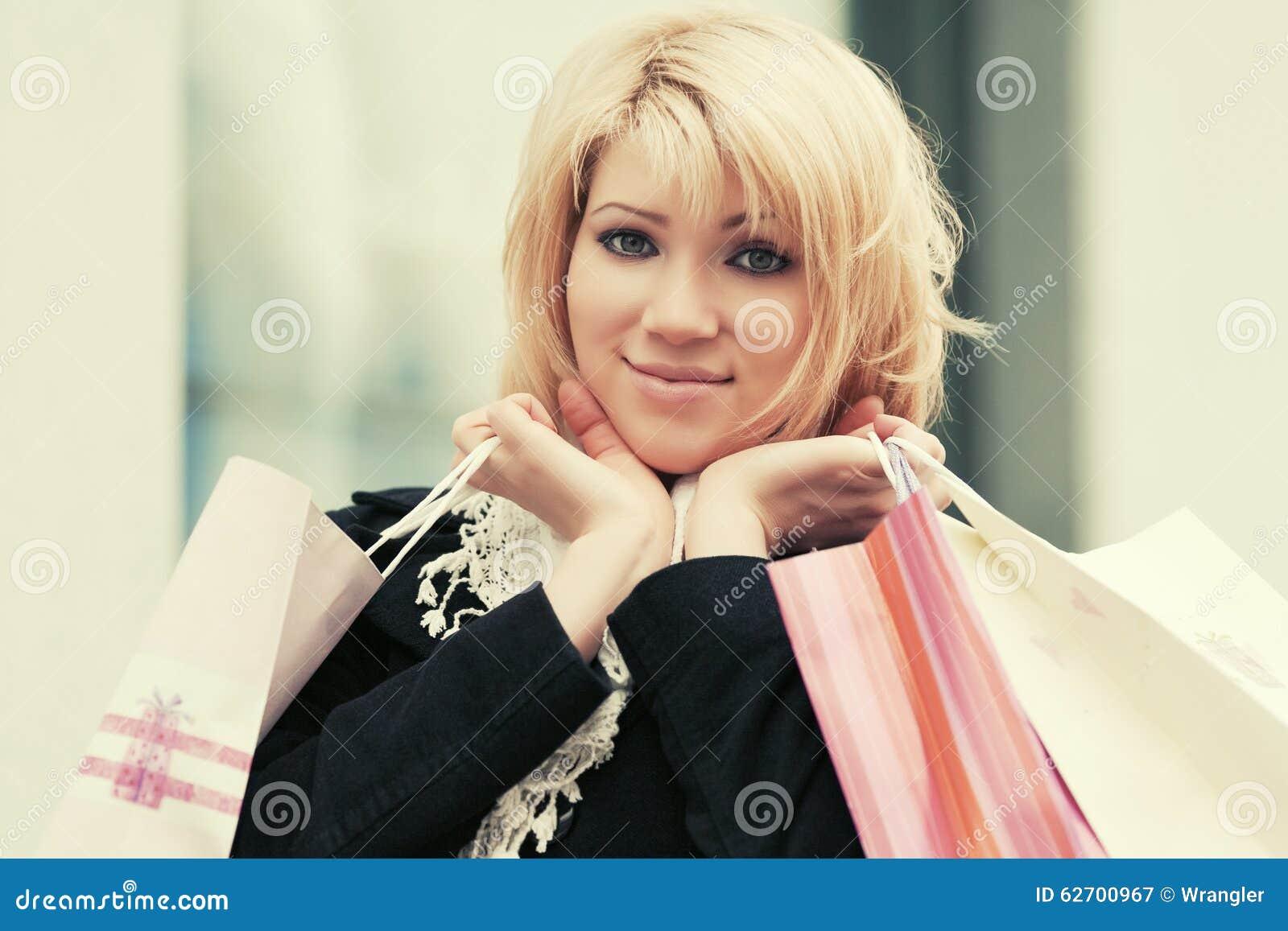Ευτυχής νέα γυναίκα μόδας με τις τσάντες αγορών