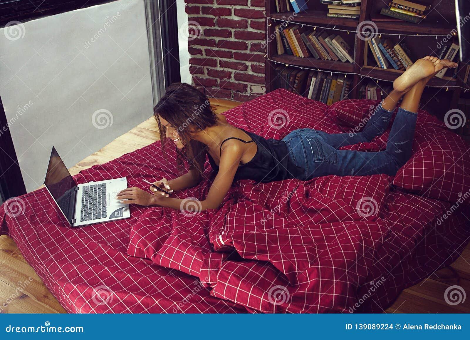 Ευτυχής νέα γυναίκα που βάζει στο ντιβάνι και που χρησιμοποιεί το lap-top στο διαμέρισμα σοφιτών - εικόνα
