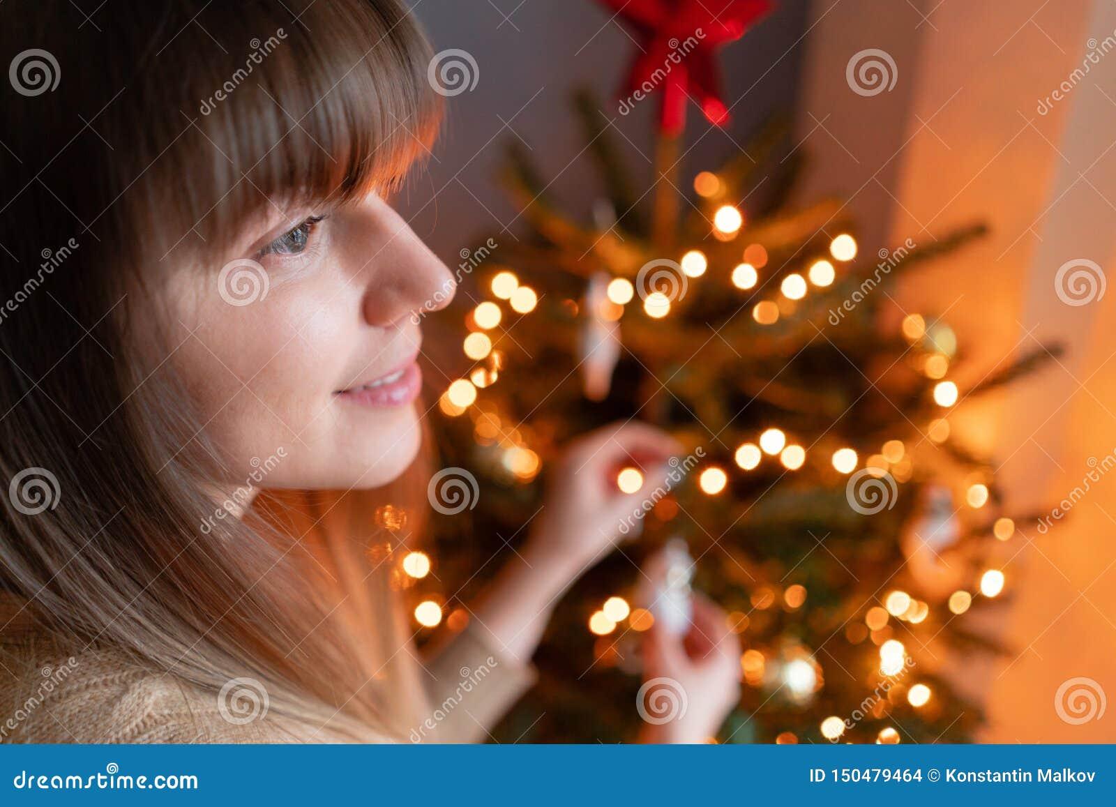 Ευτυχής νέα γυναίκα που διακοσμεί το χριστουγεννιάτικο δέντρο στο σπίτι Χειμερινές διακοπές σε ένα εσωτερικό σπιτιών Χρυσά και άσ
