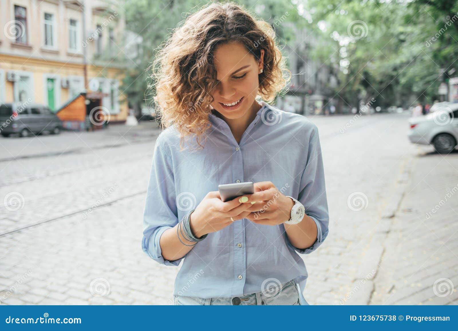 Ευτυχής νέα γυναίκα που φορά το μπλε πουκάμισο που χρησιμοποιεί το κινητό τηλέφωνο