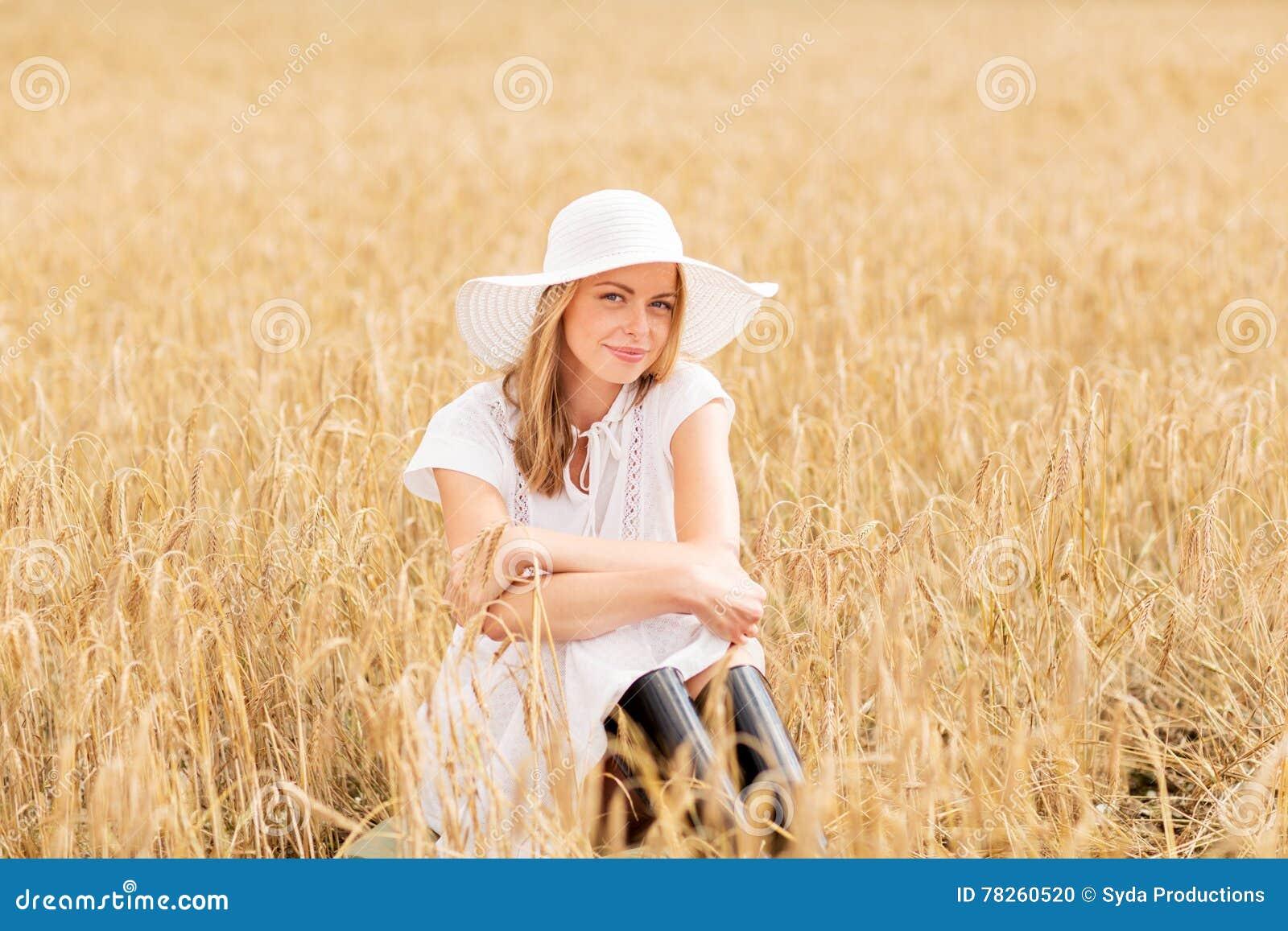 Ευτυχής νέα γυναίκα στο καπέλο ήλιων στον τομέα δημητριακών